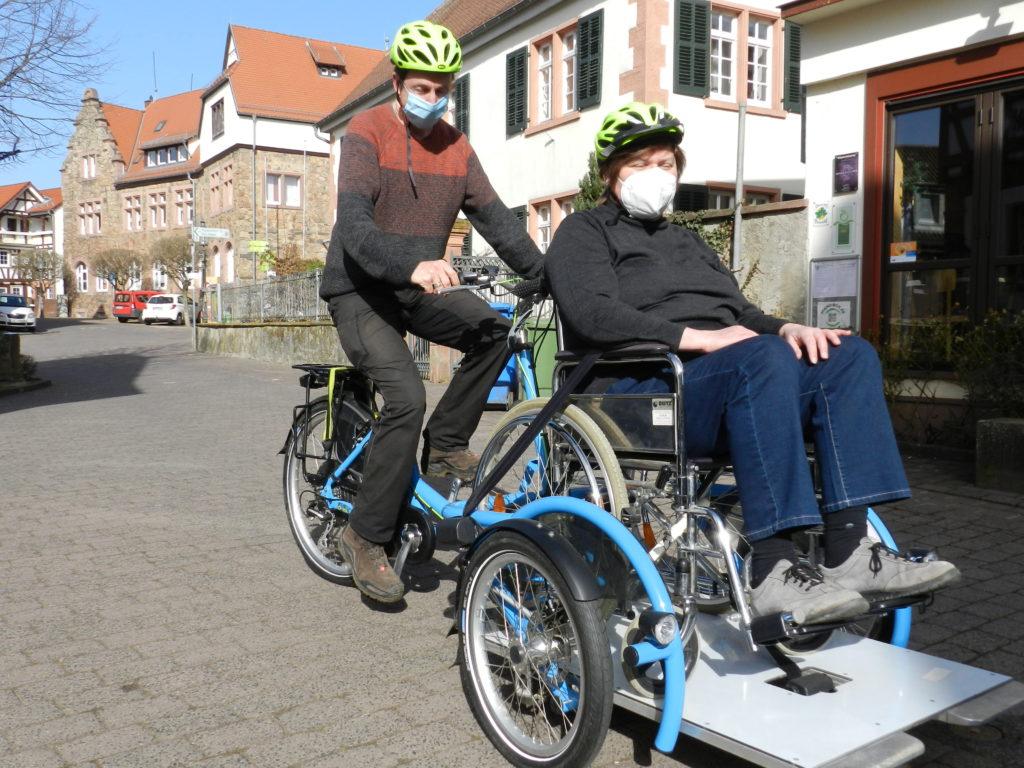 Rollstuhlrikscha mit Radfahrer und Rollstuhlfahrerin vor dem Hintergrund Rathaus Reichelsheim und Pfarrhaus 1, Reichelsheim; beide mit Fahrradhelmen und Maske