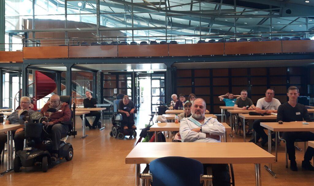 Menschen an einzelnen Tischen in der Reichenberghalle; zum Teil im Rollstuhl, zum Teil auf einfachen Stühlen